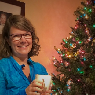 me holding a coffee by the christmas tree