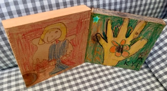 kids' crayon drawings on wood