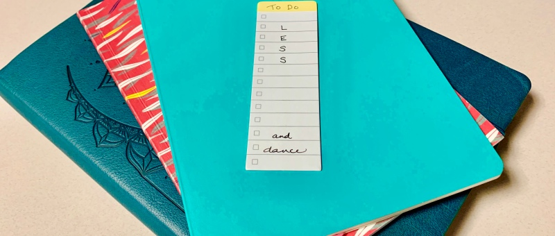 notebooks with a to do list saying LESS ... and dance