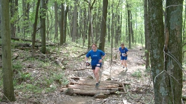 two women running through a forest