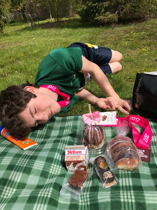 my son lying on a picnic blanket with lots of chocolate