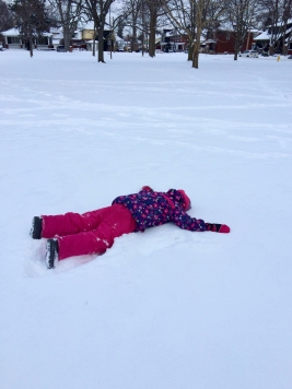 girl lying in snow face down